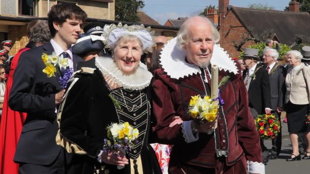 ms pan shot of shakespeare birthday celebrations with anne hathaway and shakespeare in street parade / stratford upon avon, warwickshire, united kingdom - fancy dress costume stock videos and b-roll footage