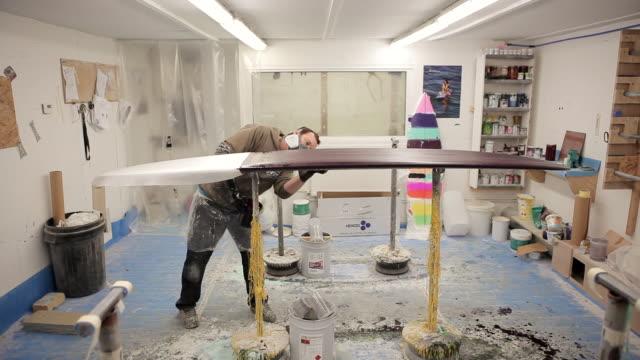 ws shot of shaper glassing surfboard / wadebridge, cornwall, united kingdom - 作業場点の映像素材/bロール