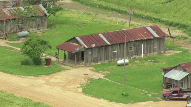 ms aerial zo shot of sharecropper shacks with people coming out from one shack / webb, mississippi, united states - sharecropper stock videos & royalty-free footage