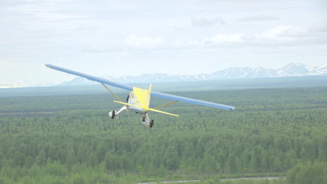MS AERIAL TS Shot of Sheldon Air Beaver en route to Denali flying over forests / Alaska, United States