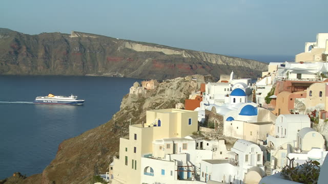 ms shot of ship moving in ocean and houses at village oia / santorini, cyclades, greece - oia santorini stock videos & royalty-free footage