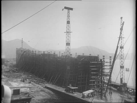 shot of shipbuilding factory with mountains in background / exterior shot of the hong kong dock company building / shot of chinese workers of the... - skeppsbyggare bildbanksvideor och videomaterial från bakom kulisserna