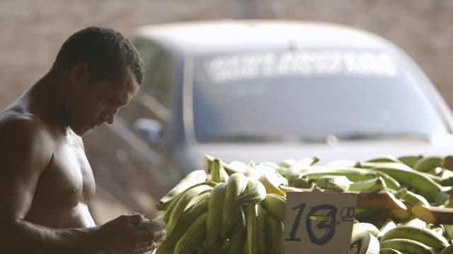 vídeos de stock, filmes e b-roll de ms tu shot of shirtless man placing price sign in front of bunches of plantains and then counting his money at mercado municipal market / manaus, amazonas, peru - banana de são tomé