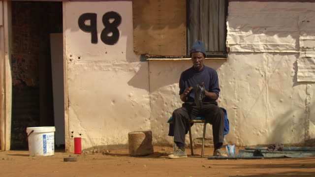 ws shot of shoe shiner working on pair of shoes / durban south africa - kwazulu natal stock videos & royalty-free footage