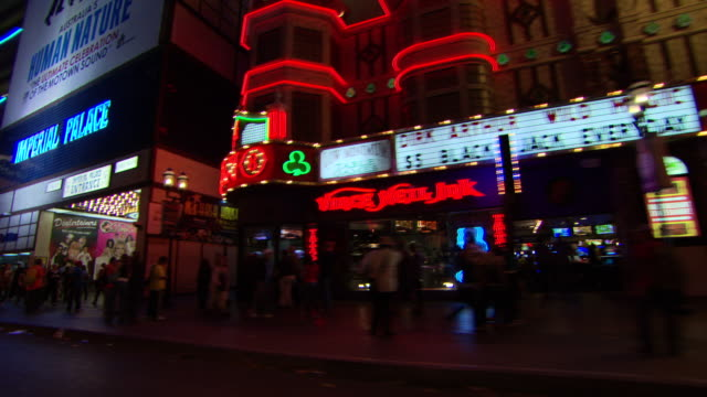 ms pov shot of shop sign and building lights illuminated in city at night / las vegars, united states - ladenschild stock-videos und b-roll-filmmaterial
