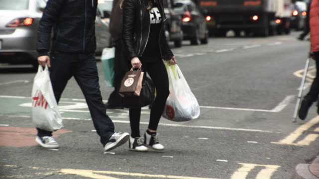 ms ts slo mo shot of shoppers crossing road with bags / united kingdom - spending money stock videos & royalty-free footage