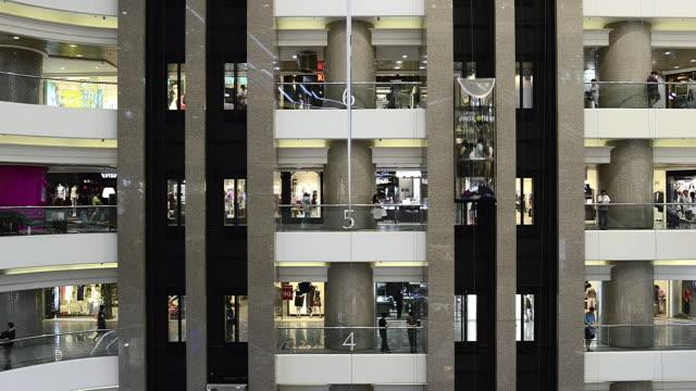 MS T/L Shot of shopping mall on pair of elevators / Hong Kong, China