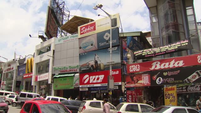 ms shot of shops and cars along city street / bangalore, india - 英字点の映像素材/bロール