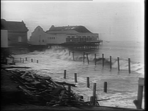 Shot of shoreline as with waves crashing amongst the piles of wood and wreckage / Wide shots of wrecked buildings and piers along the beach with...