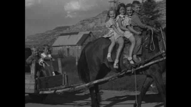 shot of short creek community / children riding on horse that is pulling wagon with children and man in it / exterior of house / man and his wife and... - mormonism stock videos & royalty-free footage