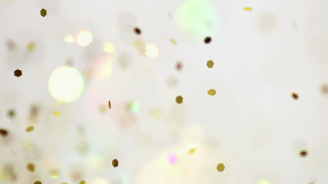 cu slo mo shot of showing flying glitters and blurred lights on white background / munich, bavaria, germany - gold coloured stock videos & royalty-free footage