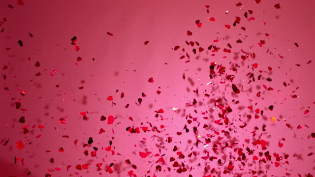 stockvideo's en b-roll-footage met shot of showing flying red glitters on pink background - roze achtergrond