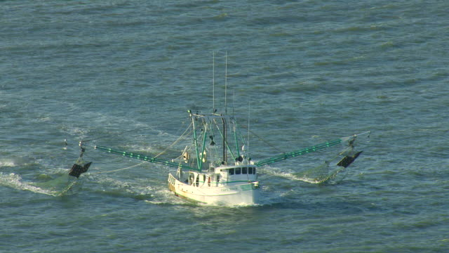 MS AERIAL Shot of shrimp boat in Mississippi Sound with nets dangling off boat in choppy water / Mississippi, United States