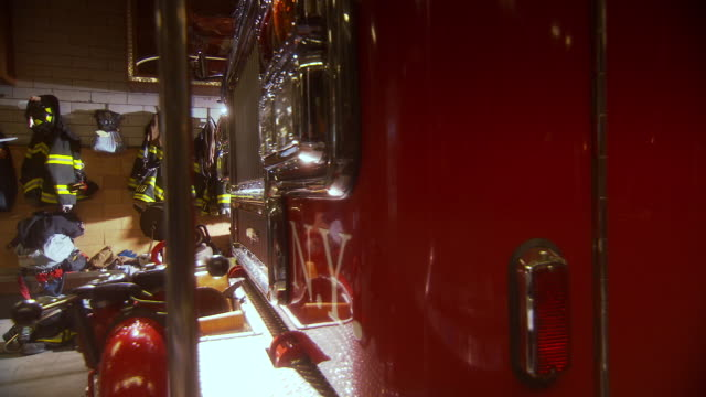 MS PAN Shot of side of fire truck and grille of fire truck with firemen uniforms hanging on wall and boots on floor in NYFD Engine Company 7 Ladder 1 fire house / New York, United States