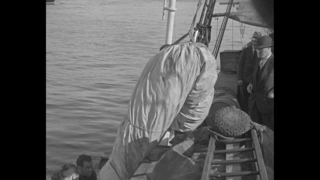 shot of side of ship with its name effie m morrissey visible / two shots of men hauling furled sails from boat onto ship / note exact month/day not... - effie stock videos and b-roll footage