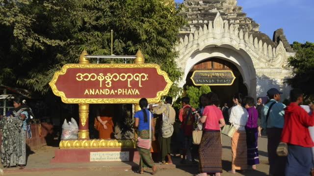 ms shot of sign and local people at entrance of ananda pagoda / bagan, mandalay division, myanmar - västerländsk text bildbanksvideor och videomaterial från bakom kulisserna