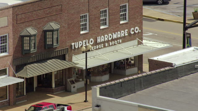 MS AERIAL Shot of sign and storefront with guitar on sidewalk outside Tupelo Hardware Store / Tupelo, Mississippi, United States