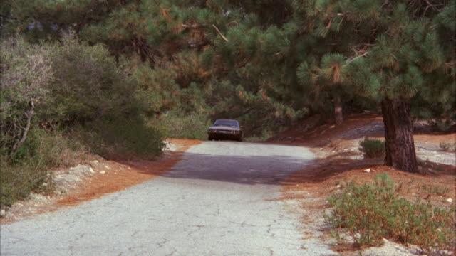 ms pan shot of sign bundesrepublik deutschland and gold citroen sedan on mountain highway  - western script stock videos & royalty-free footage