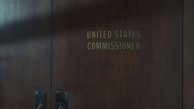 "ms shot of sign ""united states commissioner"" on door - コミッショナー点の映像素材/bロール"