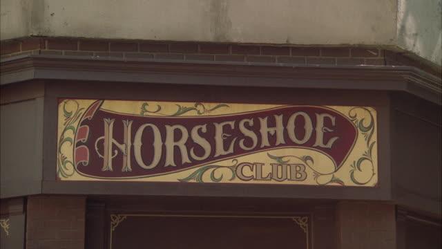 vídeos de stock, filmes e b-roll de cu shot of sign'horseshoe club' - escrita ocidental
