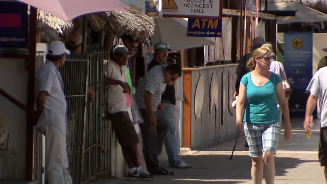 MS TD Shot of signs for shops and bars to people walking and standing around on pavement of street / Cabo San Lucas, Baja California Sur, Mexico