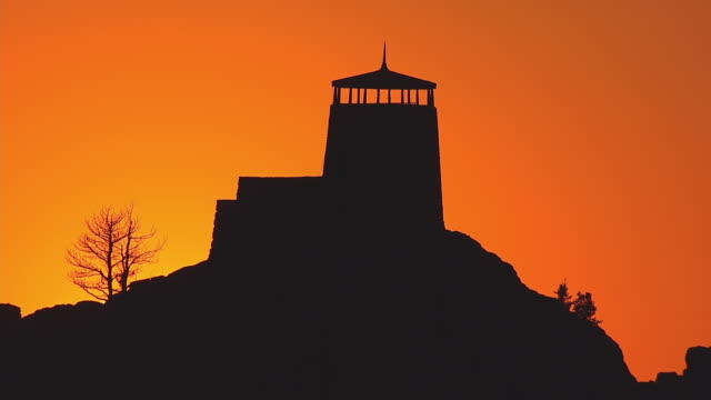 ms aerial ts shot of silhouette harney peak fire tower against bright orange back side of sun set / south dakota, united states - peak tower stock videos and b-roll footage