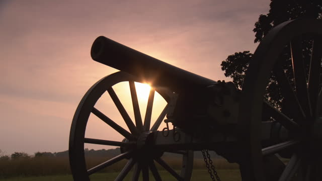 cu pan shot of silhouette of cannon at gettysburg national military park with sun rising in background  / gettysburg, virginia, united states - gettysburg stock videos & royalty-free footage