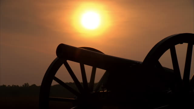 ms pan shot of silhouette of canon at dusk / gettysburg, virginia, united states - civil war stock videos and b-roll footage