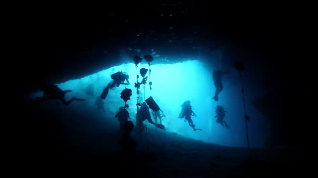 ms shot of silhouette of divers at entrance of turtle tomb cave in sipadan / sipadan, semporna, tawau, malaysia - extreme sports stock videos & royalty-free footage