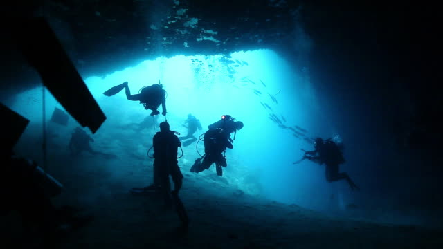 MS  Shot of Silhouette of divers at entrance of Turtle Tomb cave in Sipadan / Sipadan, Semporna, Tawau, Malaysia