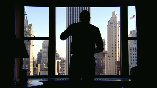 MS Shot of  silhouette of man walks into office and looks out to buildings downtown through office window / New York, United States