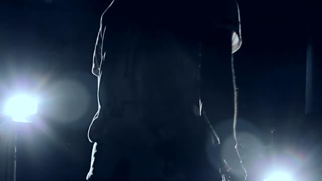 MS Shot of silhouette of young man playing bass guitar / Shinjuku, Tokyo, Japan