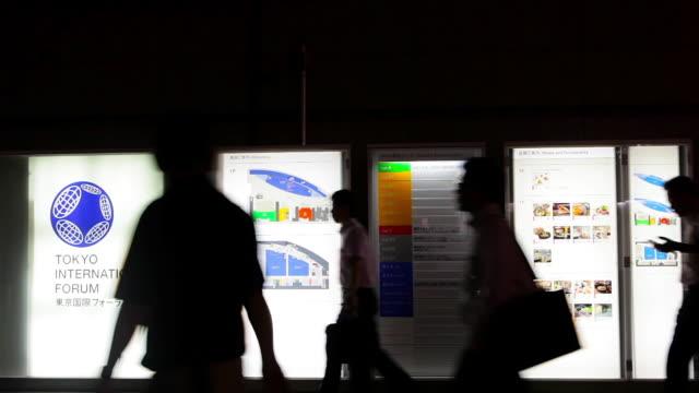ms shot of silhouette people walking by tokyo international forum directory sign / tokyo, japan - western script stock videos & royalty-free footage