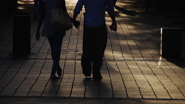 MS DA Shot of Silhouetted people walking along street in London / London, United Kingdom