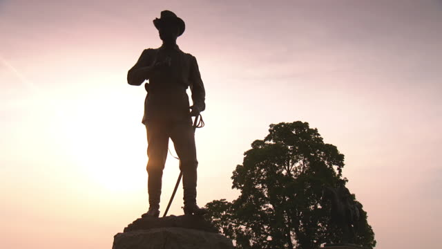 vídeos de stock e filmes b-roll de ms la shot of silhouetted statue of major general john buford at gettysburg national military park during dusk or dawn / gettysburg, virginia, united states - exército da união
