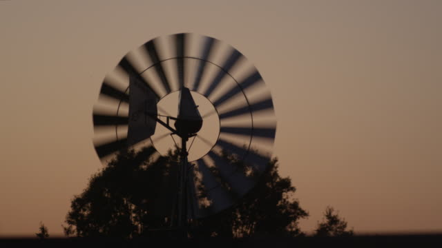 stockvideo's en b-roll-footage met cu shot of silhouetted windmill water pump during sunset / montgomery, alabama, united states - alabama
