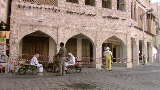 ws shot of sitting people counting money on street / doha qatar - doha stock videos & royalty-free footage