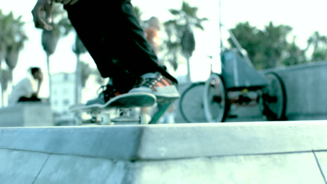 MS SLO MO Shot of skateboard riding on top of ramp and exits in air / Venice, California, United States