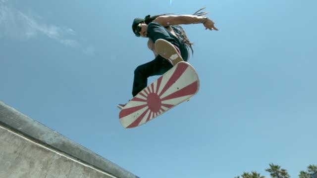MS SLO MO LA Shot of skateboarder doing front side jump in skate park / Venice, California, United States
