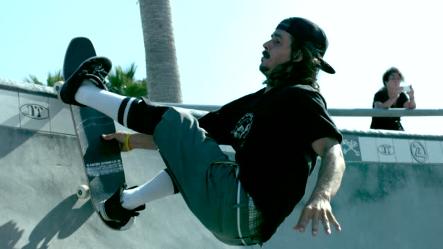 MS SLO MO Shot of skateboarder riding up bowl, bailing, and falling / Venice, California, United States