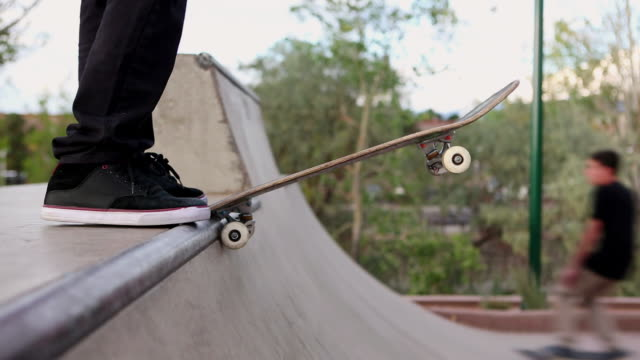 vídeos de stock, filmes e b-roll de cu shot of skateboarders dropping in on ramp / santa fe, new mexico, united states - meninos adolescentes