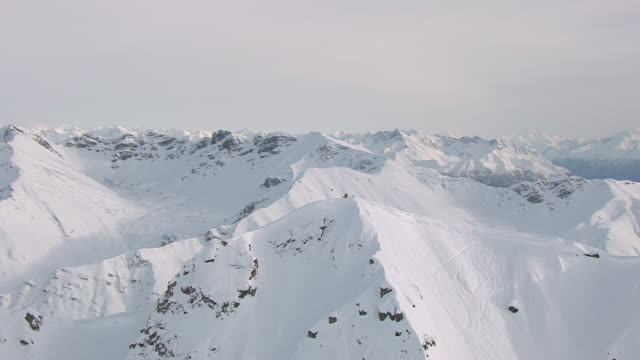MS AERIAL DS ZO Shot of skiers at top of mountain and Talkeetna mountains / Alaska, United States