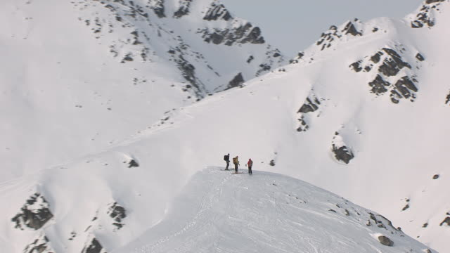 ms aerial ds zo shot of skiers at top of talkeetna mountains / alaska, united states - oben stock-videos und b-roll-filmmaterial
