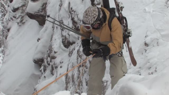 ms zo shot of skiers repelling, rock climbing down at jagged mountain peak / telluride, colorado, united states - ski pole stock videos & royalty-free footage