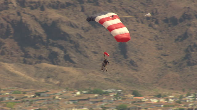 ms aerial zo ts shot of skydiver parachuting down and city with lake and mountains / boulder city, nevada, united states - clark county nevada stock videos & royalty-free footage