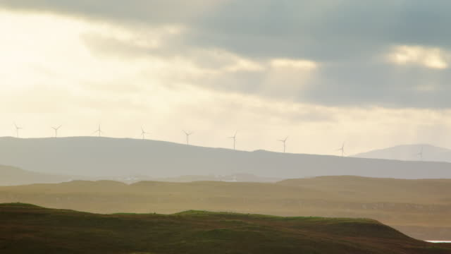 stockvideo's en b-roll-footage met ms shot of skye island wind turbines with sun rays and clouds / skye island, scotland, united kingdom - middelgrote groep dingen