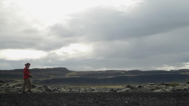 ms shot of skyline and man walking on mountain cliff / reykjavik, hofudhborgarsvaedhi, iceland  - wiese stock videos & royalty-free footage