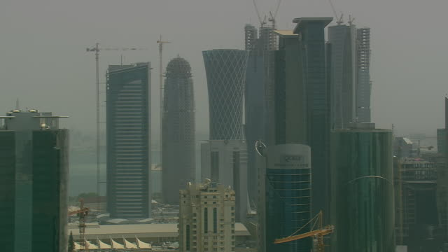 vidéos et rushes de ms aerial ds zi zo shot of skyscraper in city near ocean / qatar - qatar