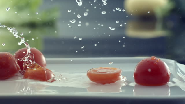 cu slo mo shot of slice of cherry tomatoes falling on plate filled with water and cherry tomatoes / seoul, south korea - cherry tomato stock videos & royalty-free footage