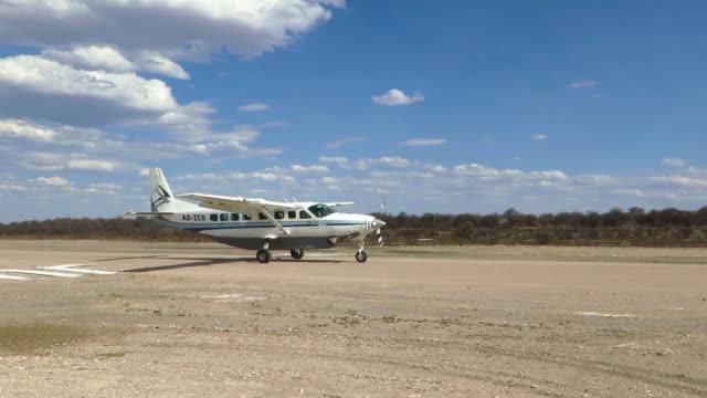 vidéos et rushes de ws pan shot of small aircraft on unpaved airstrip / kalahari plains, central kalahari game reserve, botswana - aérodrome